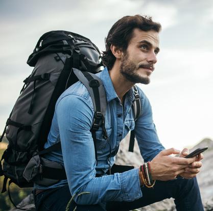 Junger, hübscher Wanderer, der sein Handy benutzt, während er sich auf dem Gipfel eines Berges ausruht